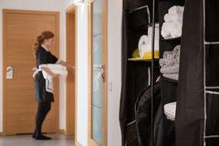 Cabinet with hygienic articles. And housekeeper cleaning the apartment royalty free stock image