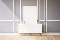 Cabinet with pictures on it, gray wall. Living room interior with an empty picture canvas standing on a small wooden cabinet with a vase with yellow flowers Stock Images