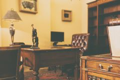 Cabinet with rich antique furniture. Cabinet with rich vintage antique wood furniture with leather chairs royalty free stock images