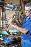 Cabinetmaker carving wood with a chisel and hammer in bench Stock Images