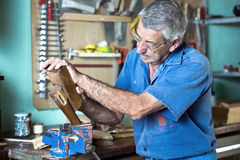 Cabinetmaker working with plane in the bench in garage at home Royalty Free Stock Images