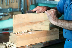 Cabinetmaker working with sandpaper in the bench in garage at ho Stock Photos