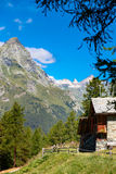 Cabins facing mountains in Italian wilderness Royalty Free Stock Photo
