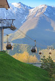 Cabins of funicular on the background of green grass and snow-capped mountains Royalty Free Stock Photography