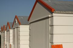 Cabins in a row. On the seaside, storage on the beach, sunny days, wooden cabins, red, white, grey, blue skies Stock Photos