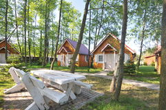 Cabins and trees. A few small wooden cabins surrounded by trees, a table with benches in the foreground Royalty Free Stock Images