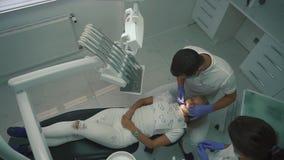Cabitet del dentista durante le procedure Specialista dentario che controlla salute paziente della cavità, quando dare di aiuto stock footage