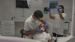 Cabitet del dentista durante le procedure Specialista dentario che fa ispezione per salute della cavità, quando assistente che gu video d archivio