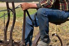 Cablaggio della tenuta dell'agricoltore mentre sedendosi su un vecchio sedile del disco Fotografia Stock