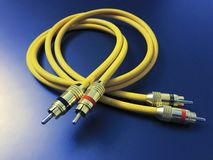 Cable amarillo de la extensión audio estérea aislado en fondo azul imagen de archivo