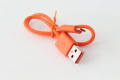 Cable anaranjado del USB en el fondo blanco Foto de archivo libre de regalías
