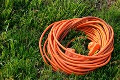 Cable anaranjado en la hierba Fotos de archivo libres de regalías
