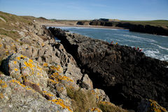 Cable bay. Along the Wales coast path, Cable bay, Anglesey, Wales, UK. A group on the rocks coasteering with the sea and beach in the background Royalty Free Stock Photo