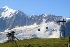 Cable-car against the white snowy Swiss mountains. The mountain of First is a minor summit below the Schwarzhorn in the Bernese Alps in Switzerland. It is mostly royalty free stock image