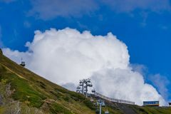 Cable car on a background of mountains and blue sky with clouds in Krasnaya Polyana. Royalty Free Stock Image