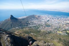 Cable car cabin is approaching the station. View on Cape Town and Signal Hill from the top of Table Mountain. View on Cape Town and Signal Hill from the top of stock photo