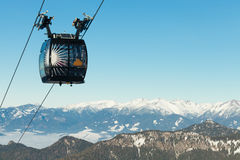 Cable car cabin going up above the clouds to the very top of a mountain with a beautiful scenery on background. Cable car cabin going up above the clouds to the royalty free stock photography