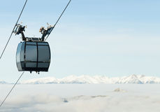 Cable car cabin going up above the clouds to the very top of a mountain at a ski resort. Cable car cabin going up above the clouds to the top of a mountain at a stock photography