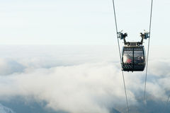 Cable car cabin going up above the clouds to the very top of a mountain at a ski resort area. Cable car cabin going up above the clouds to the top of a mountain royalty free stock photography