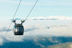 Cable car cabin going to the top of a mountain above the clouds at a ski resort. Cable car cabin going up to the very top of a mountain at a ski resort royalty free stock image