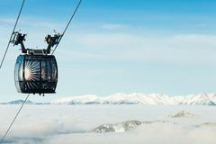 Cable car cabin moving to the top of a mountain above the clouds. Cable car cabin moving to the very top of a mountain stock photo