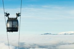 Cable car cabin moving to the top of a mountain above the clouds at a ski resort. Cable car cabin moving to the very top of a mountain at a ski resort stock photos