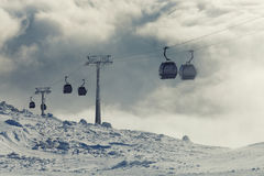 Cable car cabins going up and down high in the mountains at a winter sports resort area on a cloudy day Royalty Free Stock Images