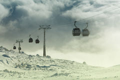 Cable car cabins going up and down high in the mountains at a winter sports resort area on a cloudy day. Filtered image: cross pro Stock Images