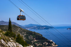 Cable car gondola against clear sky and ocean Stock Photo