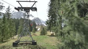View from Cable car gondola moving in Lake Lucerne area of Pilatus mountains in Swiss Alps in Switzerland. Cable car gondola moving in between green trees stock video footage