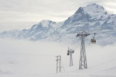 Cable car gondolas move skiers uphill at the ski resort in Grindelwald, Switzerland. Royalty Free Stock Images