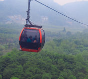 Cable Car on Green Epic Scenery Background. Cable Cabin on Ropeway on Green Landscape Stock Photo
