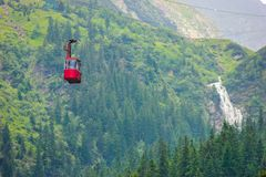 Cable car with green woods and Balea Cascada waterfall. Background in Sibiu, Romania Stock Photos