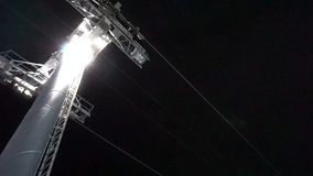 Cable car lift at ski resort. Night skiing from the mountains. stock video footage
