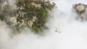 Cable Car through the Mist, Autumn. Aerial panorama of a scenic cable car flying over the beautiful autumn valley Stock Image