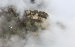 Cable Car through the Mist, Autumn. Aerial panorama of a scenic cable car flying over the beautiful autumn valley Royalty Free Stock Photography
