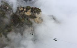 Cable Car through the Mist, Autumn. Aerial panorama of a scenic cable car flying over the beautiful autumn valley Royalty Free Stock Photo