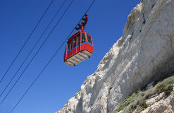 Cable car on mountain. Red cable car on side of mountain, blue sky background Royalty Free Stock Image