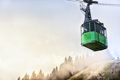 Cable car with passengers descending from the top Stock Photos