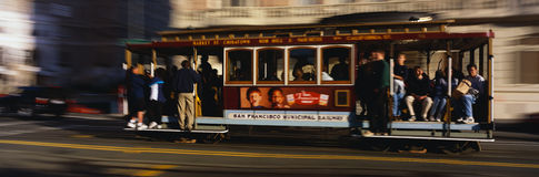 Cable Car riding from Nob Hill. This is a Cable Car riding from Nob Hill. There are passengers holding on to the poles, standing and also sitting down in the Stock Image