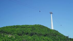 Cable car ropeway above the green forest mountain with summer blue sky view.
