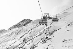 Cable car at a ski resort. Chairlift with skiers. Mountains covered with snow. And cloudy day. Black and white picture royalty free stock image