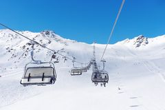 Cable car at a ski resort. Skiers ascend the mountain in the chair lift. A Sunny weekend in the Alps stock photo