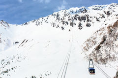 Cable car on snow covered mounytain under blue sky. Cable car on snow covered mountain under blue sky, Japan Northern Alps Stock Image