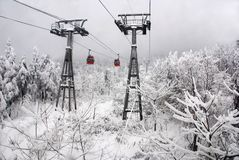 Cable car in snow scenery. Cable cars take people to the deep mountain in winter. Xiling Snow Mountain is a national scenic resort, which lies in Sichuan Stock Photography