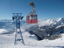 Cable car in Swiss Alps. Cable car travelling over ski slope in resort of Crans Montana with Alps mountains in background, Valais, Switzerland Stock Photos