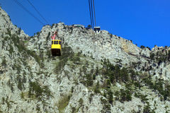 Cable car to mount Ai-Petri, view from the cabin funicular to the mountain top. And descending yellow booth stock photo