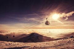 Cable car in winter mountain, inverse scenery in sunrise. Or sunset royalty free stock photo