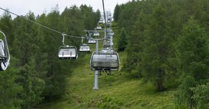 Cable cars going up in austrian alpen during stron wind royalty free stock photo