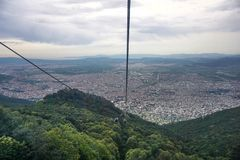 Cable cars going up in to the mountain, green hills royalty free stock photography